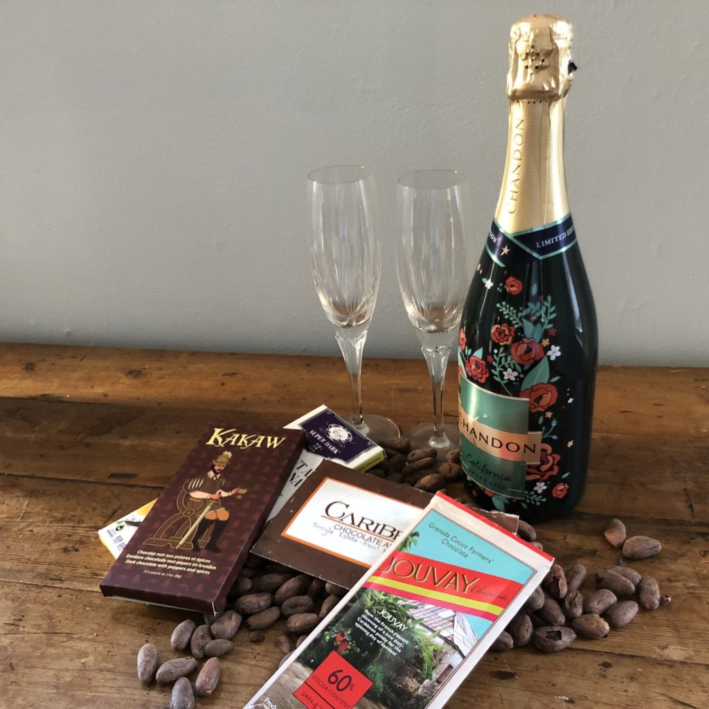 champagne bottle with two glasses and an assortment of fine chocolate bars over cacao beans