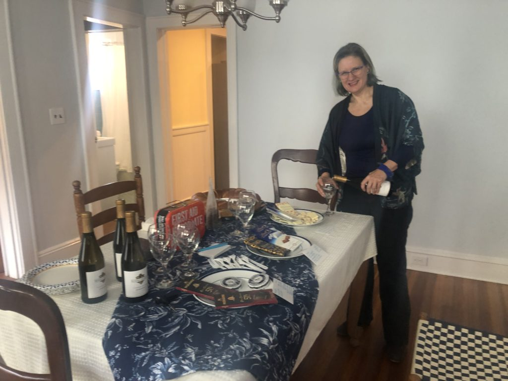 Stacey pouring wine at a table set up with wines & chocolates for a tasting