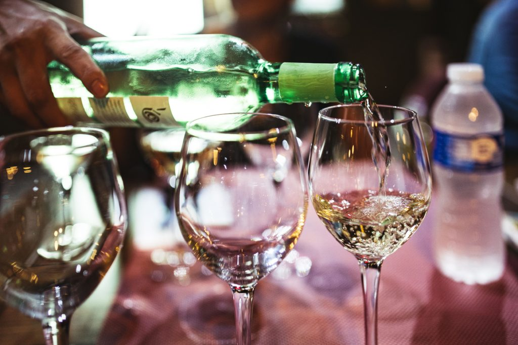 wine being poured into glasses for tasting