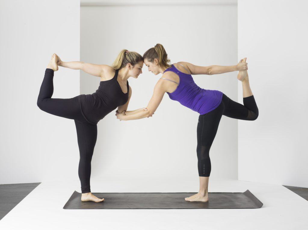 two women in yoga poses as a way to follow their passion
