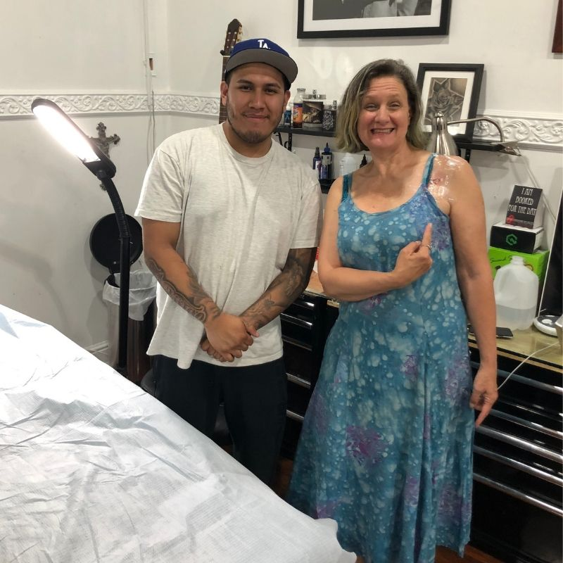 Me showing off my tattoo standing next to the artist