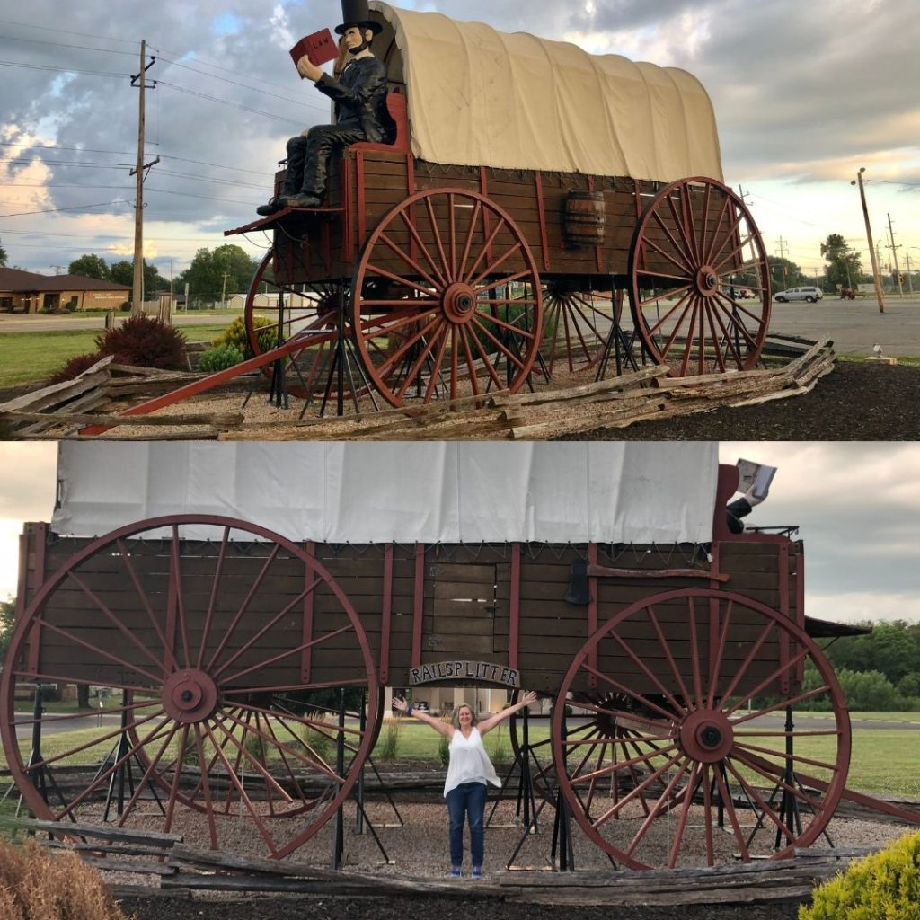 Largest Covered Wagon with Abe Lincoln statue as well as Stacey standing by the huge wagon wheels