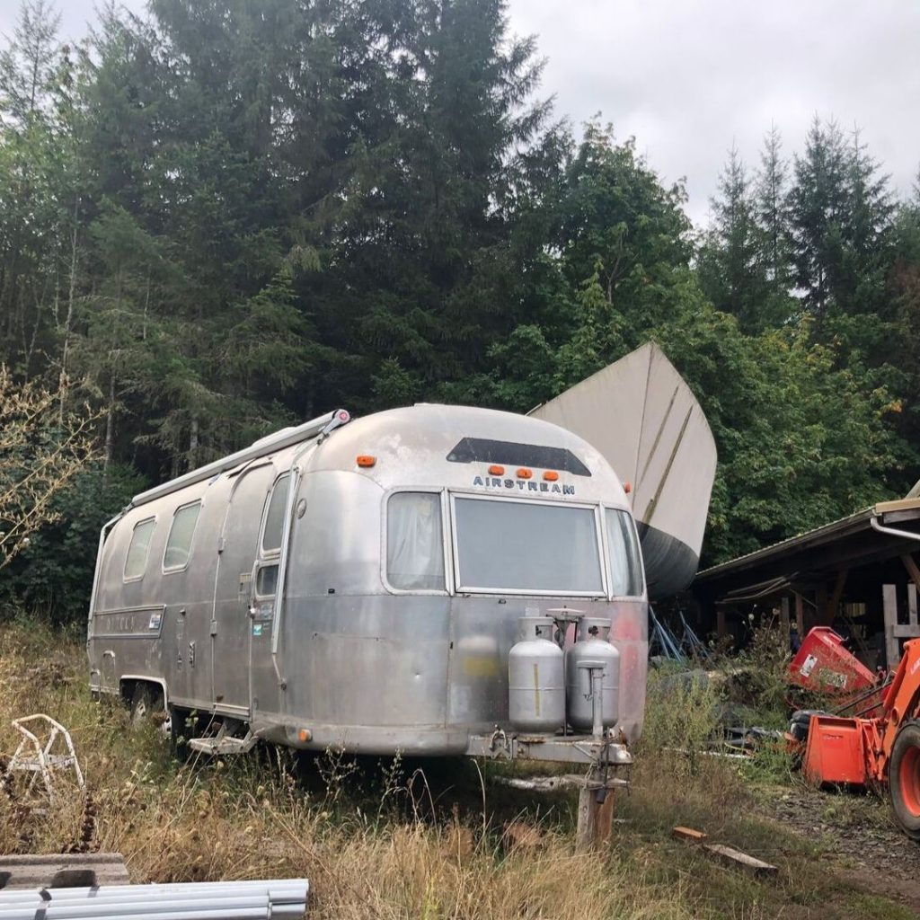 front view of 1975 Airstream with seller's boat behind it. Wednesday our Airstream Adventure