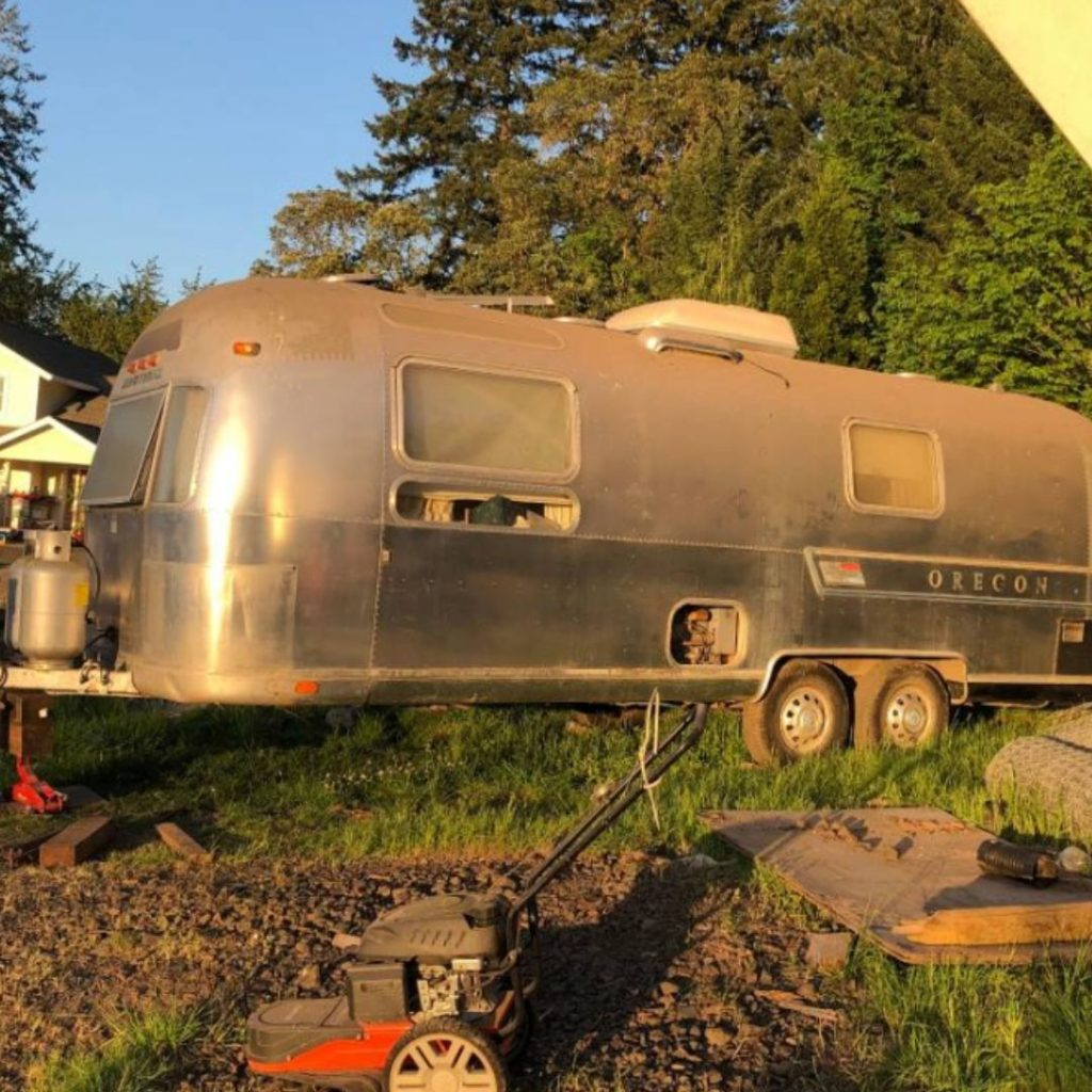 used vintage Airstream sitting in someone's backyard