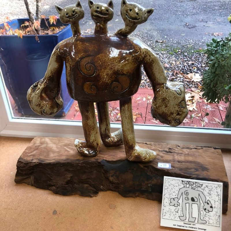 Artist at play, creating a 3 headed monster in ceramic displayed on a window sill