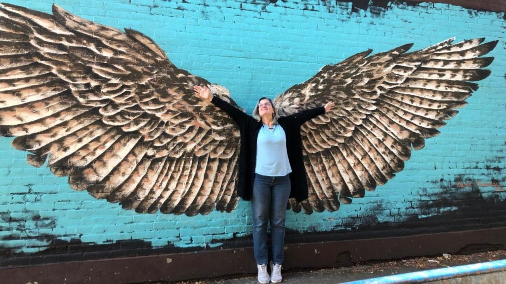Me standing in front a mural of wings