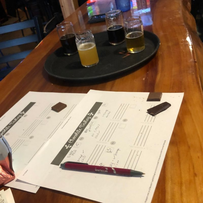 4 beer tasting glasses on tray, behind chocolate map for pairing notes