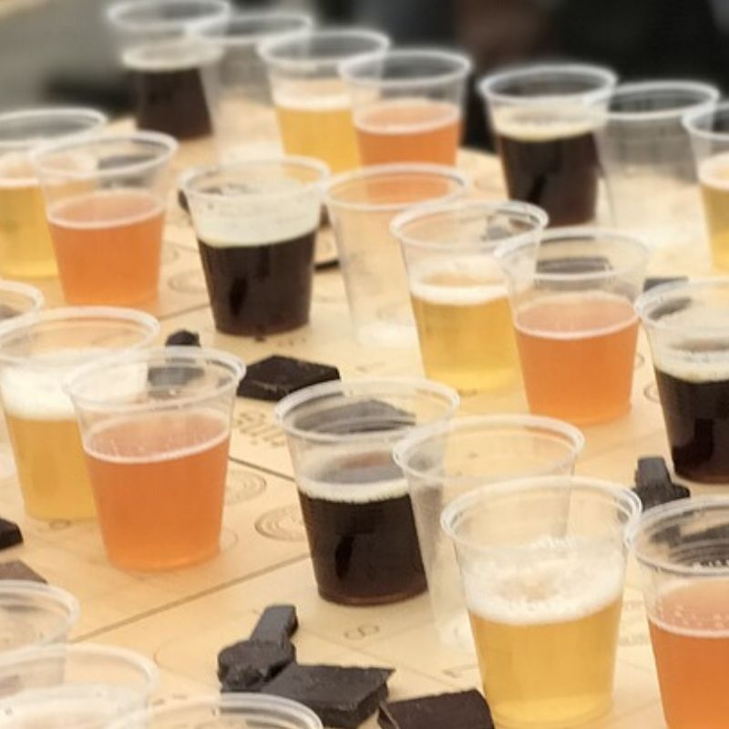 rows of plastic cups filled with beers and bits of chocolate next to them
