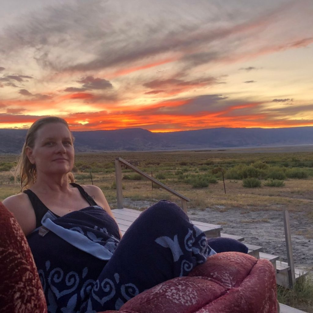 Stacey relaxing on a red couch with a mountain sunset behind her