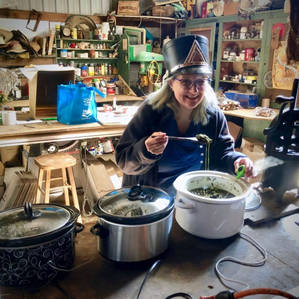 Stacey in marching band hat stirring crock pot of ingredients
