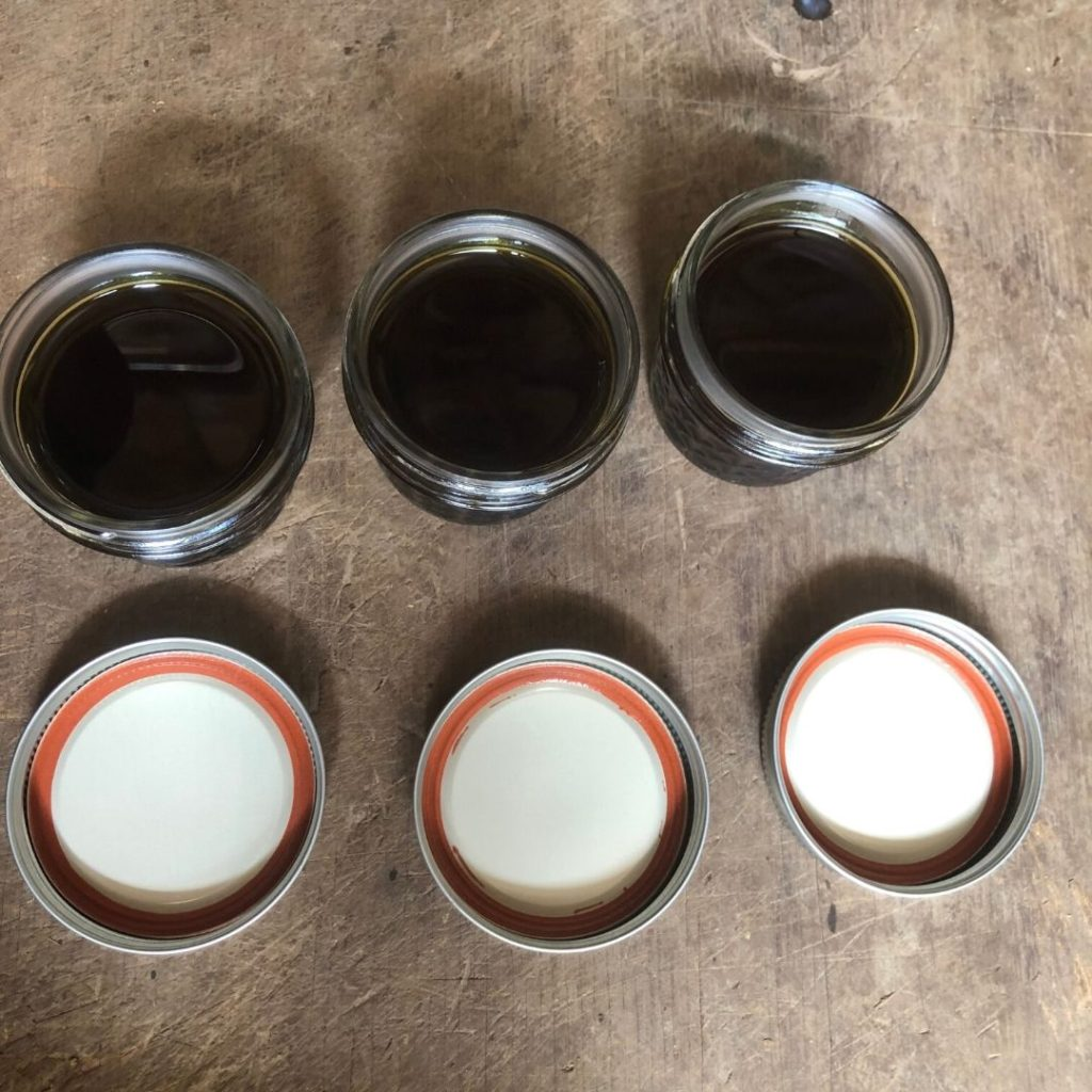 3 small jars with green liquid, and their lids