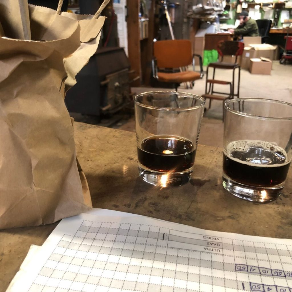 two glasses of ale next to a paper bag