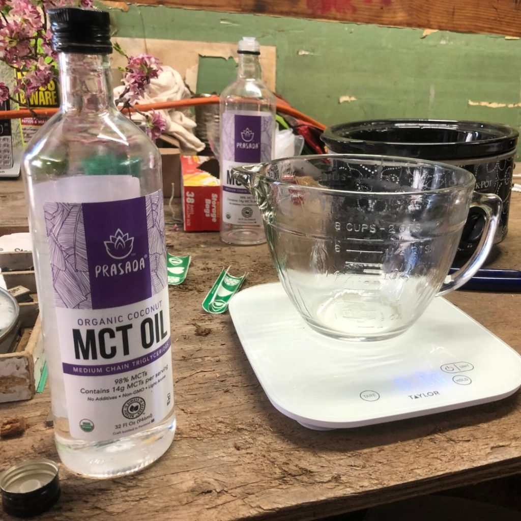 bottle of MCT oil next to glass measuring cup