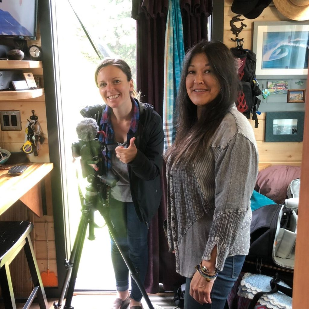 Jenna and Brenda standing in front of the tiny house door, inside