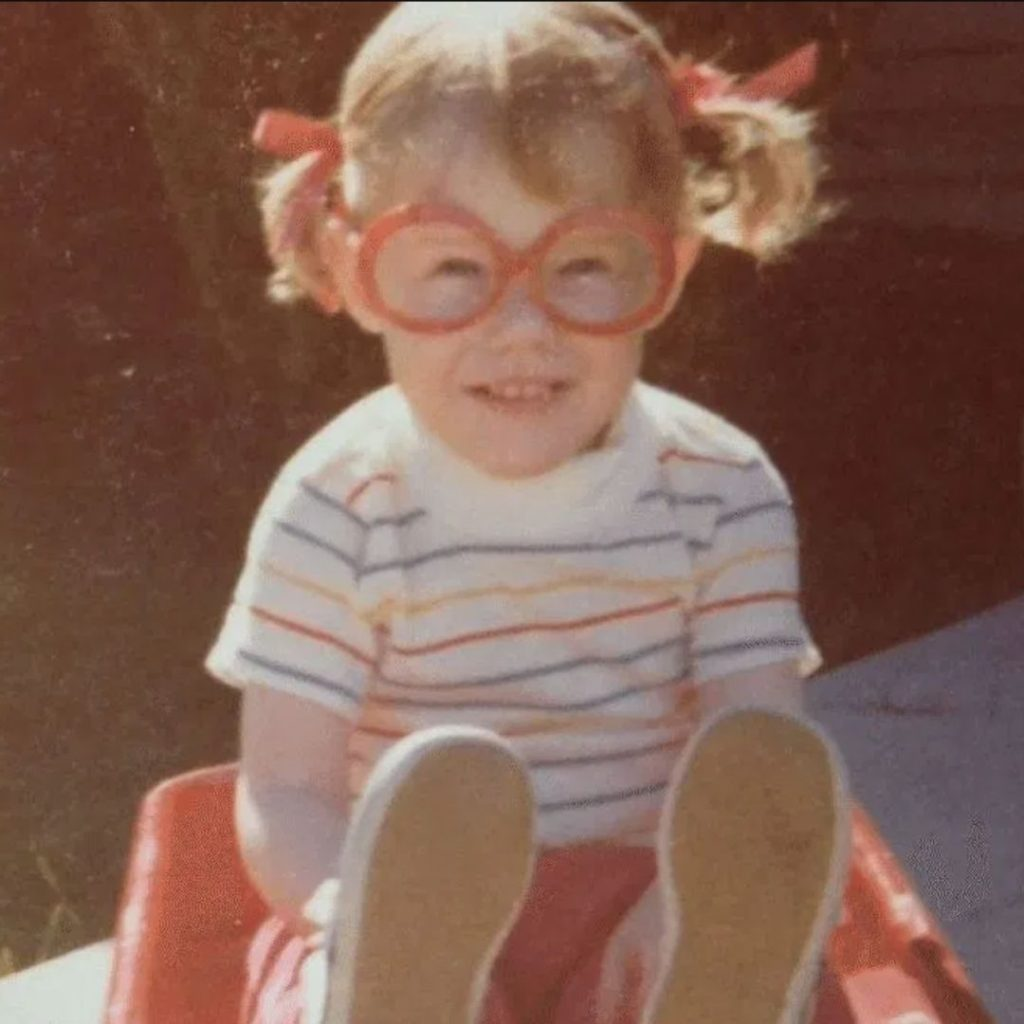 Kara, as a young child in red glasses, who is the founder of Playgrounding Podcast