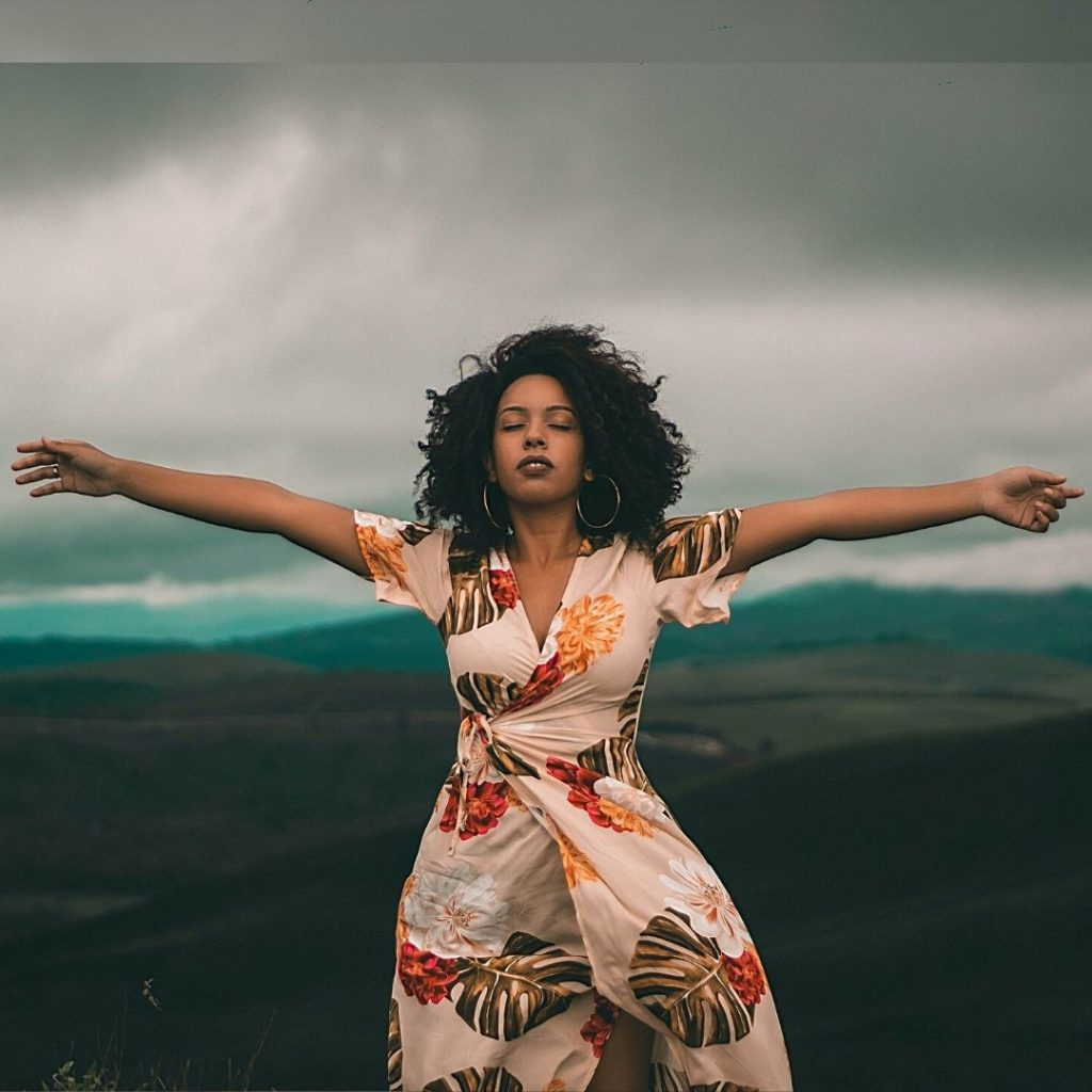 woman arms spread against grey sky with her eyes closed