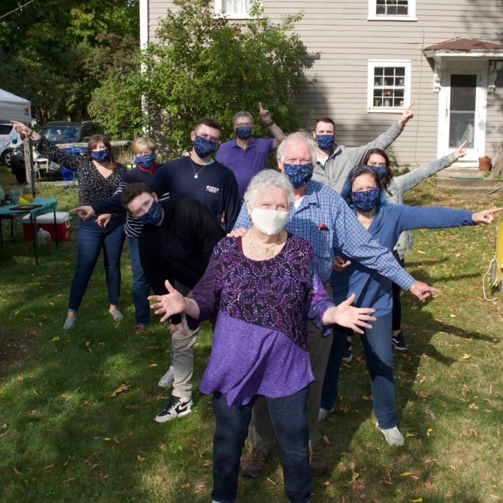 Family in pandemic masks with grandma in front and rest posing behind her