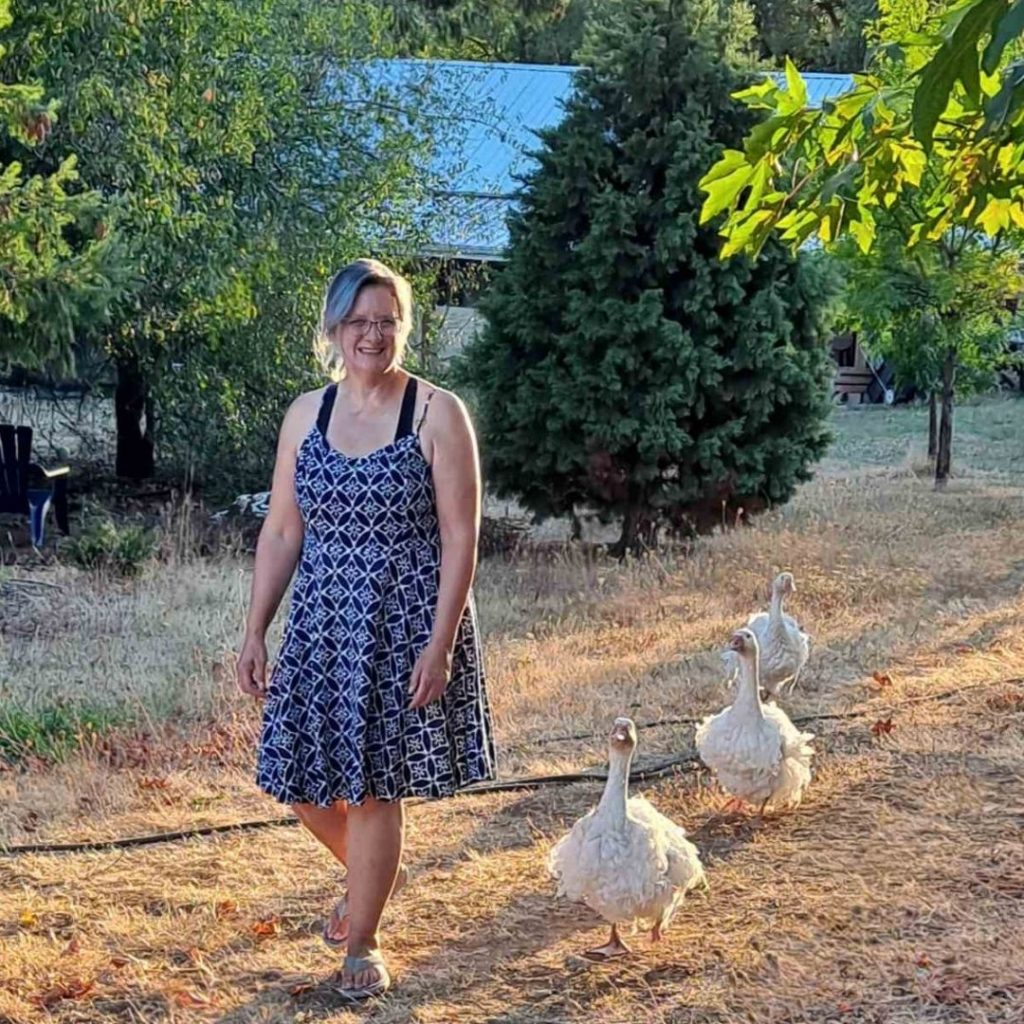 Stacey walking with three geese following behind her