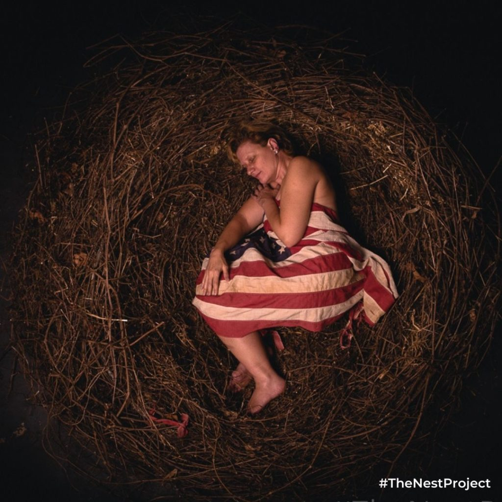 Stacey covered by American flag as part of The Nest Project