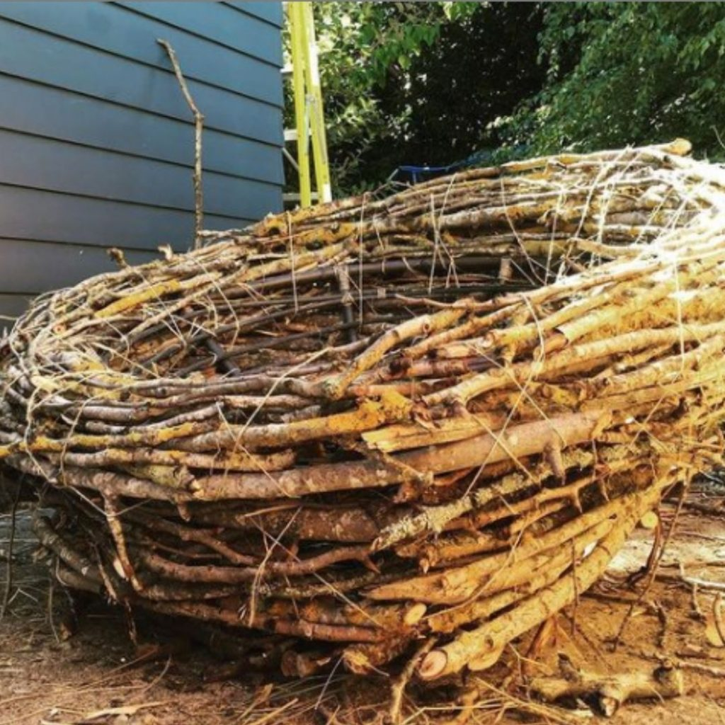 A human-sized nest built with branches by the side of a house