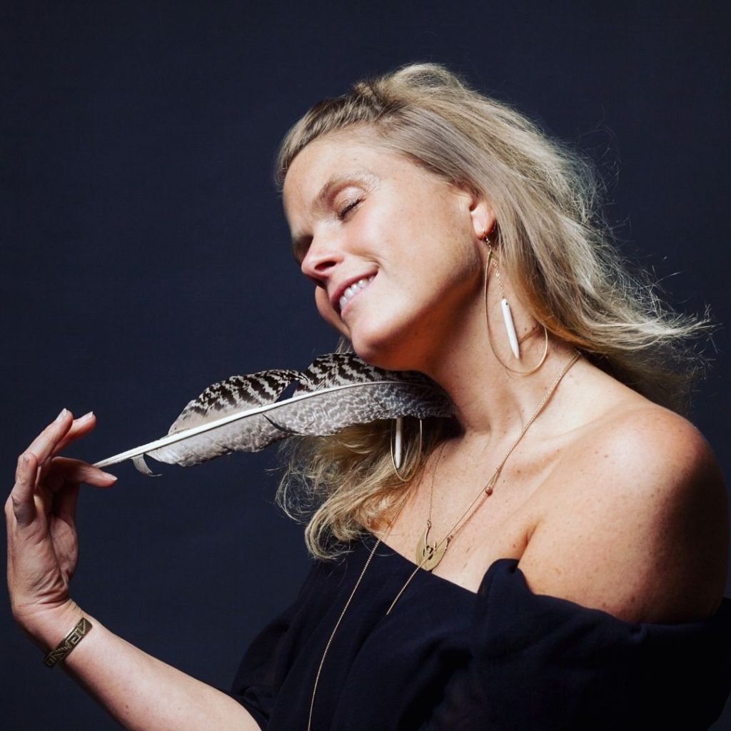 Debbie Baxters holding a feather to her cheek