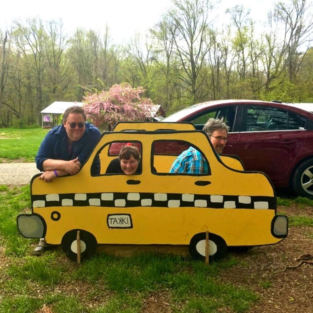 three people, outside, sitting in bright yellow wooden bench that looks like a taxi.